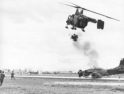 An HH-43 equipped with a fire bottle is the first to arrive over an A-1E that bellied in at Da Nang AB.